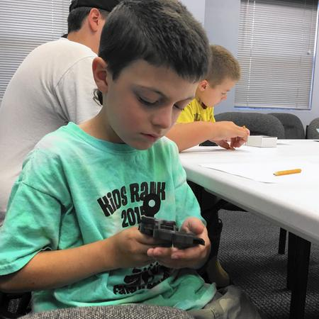 Seven-year-old Henry Heun, of Highland Park, learns how to use a compass during a program at the Great Lakes Naval Museum Saturday.