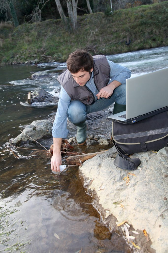 A scientist testing water quality of a river.